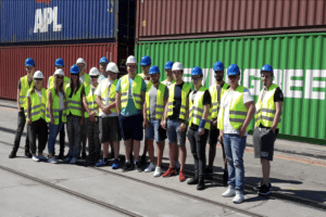 mehrere Auszubildende mit Helmen vor großen Containern